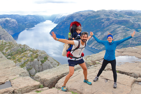 Photo for A cheerful couple and their little kid in the summit of the Pulpit Rock (Preikestolen), one of the world's most spectacular viewing points. A plateau that rises 604 meters above the Lysefjord, Norway. - Royalty Free Image