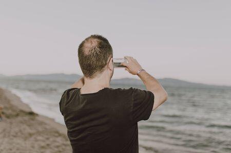 Photo pour Man on the beach making a call - image libre de droit