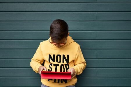 Photo pour Boy with yellow sweatshirt surfing with his tablet . Wooden green Background - image libre de droit
