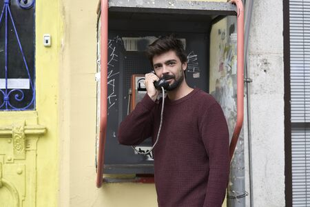 Young man making a a call in a telephone booth