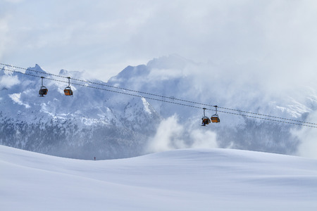 Skiing on the dolomites, Cabs for skiers above the horizon in the background mountains. Val di Fiemme, Italy.