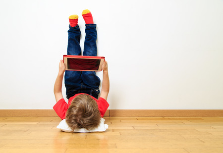 Photo pour little boy looking at touch pad at home - image libre de droit
