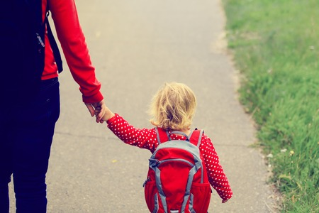 Photo pour Mother holding hand of little daughter with backpack going to school or daycare - image libre de droit