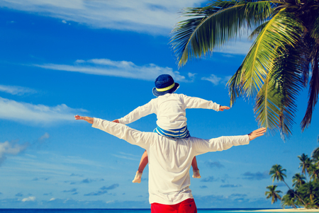 Photo pour happy father and little son on shoulders play on sky at tropical beach - image libre de droit