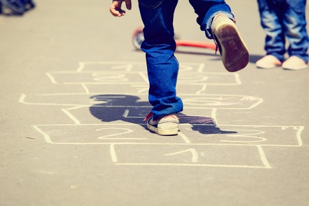 Foto de kids playing hopscotch on playground outdoors, children outdoor activities - Imagen libre de derechos