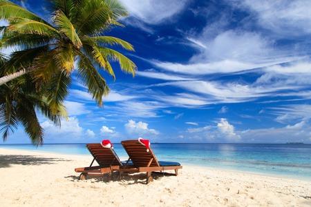 Foto de two chair lounges with red Santa hats on tropical summer beach - Imagen libre de derechos