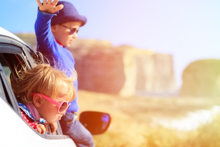 Foto de happy little boy and girl travel by car in mountains, kids travel - Imagen libre de derechos