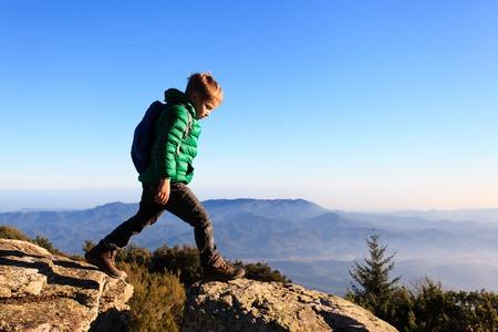 Foto de little boy with backpack hiking in scenic mountains, kids travel - Imagen libre de derechos