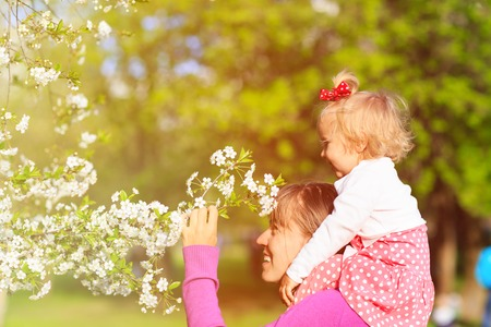 mother and little daughter enjoy spring blossom, spring concept