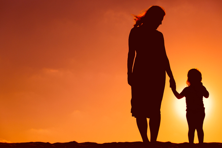 Photo for silhouette of mother and daughter holding hands at sunset - Royalty Free Image