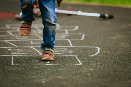 Foto de little boy playing hopscotch on playground - Imagen libre de derechos