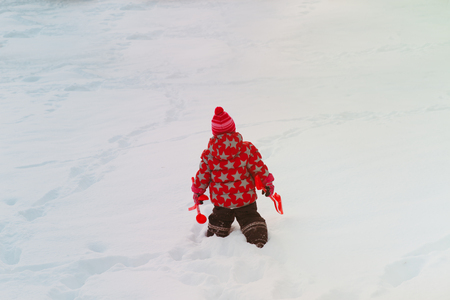 little girl go play in winter snow
