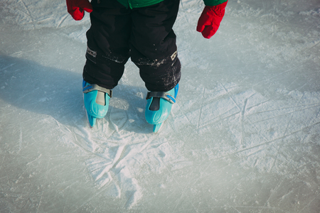 child learning to skate on ice in winter snow