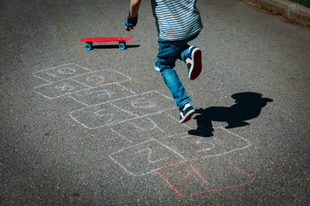 Photo pour little boy playing hopscotch on playground - image libre de droit