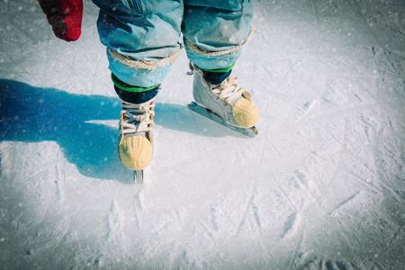 baby learning to skate on ice in winter snow