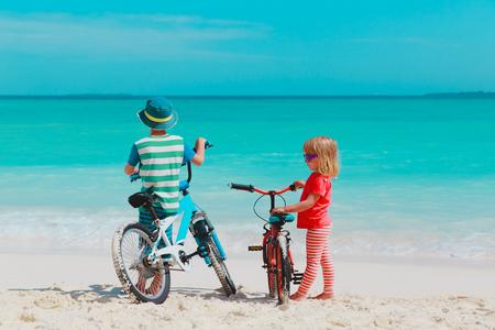 Photo pour little boy and girl ride bike on beach - image libre de droit