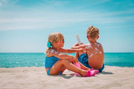 Photo for sun protection, little girl and boy with sun cream at beach - Royalty Free Image