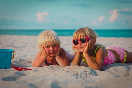 Foto für cute happy little girls play with sand on beach - Lizenzfreies Bild
