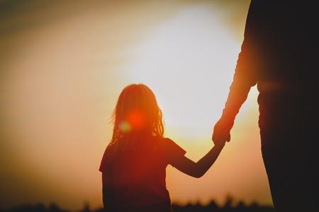Photo pour silhouette of little girl holding parent hand at sunset - image libre de droit