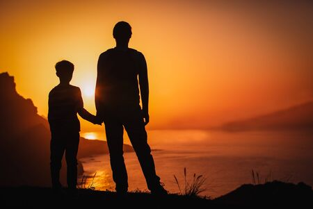 silhouette of father and son holding hands in sunset nature