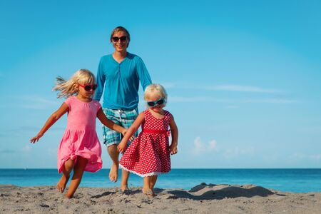 Photo pour happy family -father with cute little daughters play at beach - image libre de droit