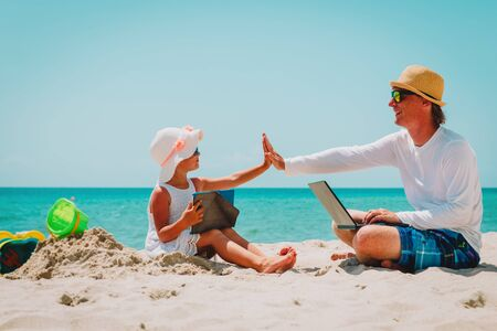 Photo for happy father with laptop and cute daughter with touch pad at beach - Royalty Free Image