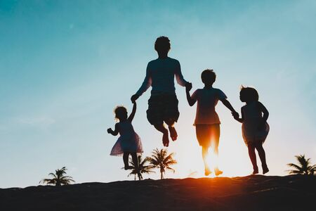 Photo for happy family on beach - father with kids jumping from joy at sunset - Royalty Free Image