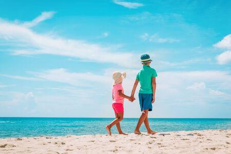 Photo pour little boy and girl walk on summer beach - image libre de droit