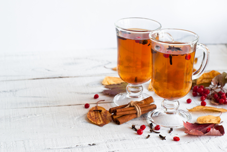 Photo pour Autumn hot tea with spices in glass cup and falling leaves around. - image libre de droit