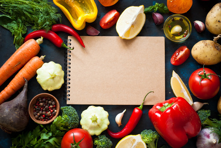 Ingredients for cooking. Fresh vegetables, notepad and spices on dark table. Food background.