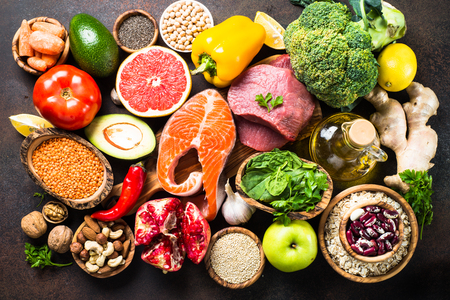 Foto de Balanced diet food background. Organic food for healthy nutrition, superfoods. Meat, fish, legumes,  nuts, seeds, greens, oil and vegetables. Top view on dark stone table. - Imagen libre de derechos