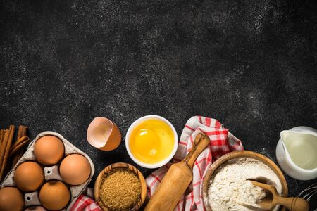 Photo for Baking background on black table. Flour, sugar, eggs, spices and utensil on black background top view with copy space. - Royalty Free Image