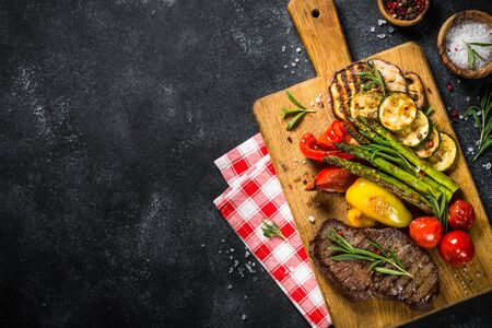 Photo pour Beef steak grilled with vegetables on black stone table. Barbecue dish. Top view. - image libre de droit