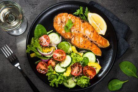 Photo pour Grilled salmon fish steak with vegetables on black. - image libre de droit