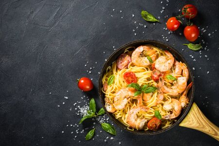 Photo pour Pasta seafood. Pasta Spaghetti with shrimp, cream sauce and basil. Top view on black stone table. - image libre de droit