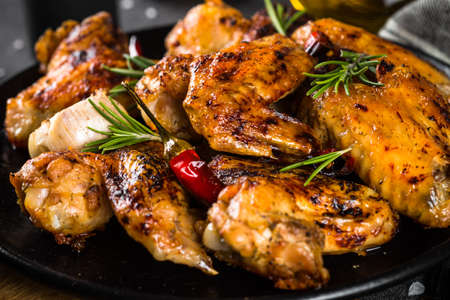 Photo pour Grilled chicken wings with spices in black plate. - image libre de droit