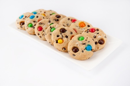 Beautiful cookies with multi-colored jelly beans on a white rectangular plate