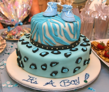 Two tier baby shower cake with marzipan icing and baby shoes as decoration