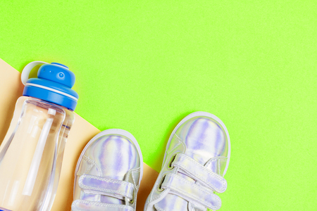 Child sneakers and bottle of water on green background. Top view, flat lay. Copyspace for text. Children healty lifestyle concept.