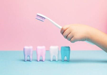 Photo pour Child's hands holding big tooth and toothbrush on pink backgroubd. Healty care teeth concept. Top view, flat lay. Copy space for your text. - image libre de droit