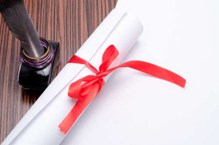 parcel with a feather and an inkwell on a table