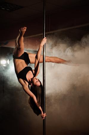 Photo pour attractive sexy woman on the pole dancer performing - image libre de droit