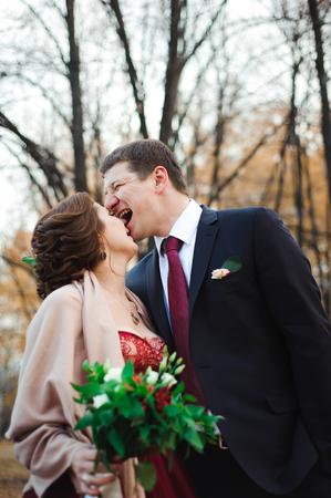 Photo pour happy bride and groom walking in the autumn forest - image libre de droit