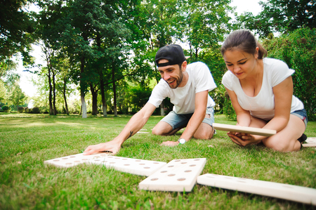 Photo pour Domino players on the grass. Young man and woman playing giant dominoes in the Park on the grass - image libre de droit