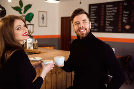Photo pour Beautiful Woman And Handsome Man Drinking Coffee While Spending Time In Coffee Shop. - image libre de droit