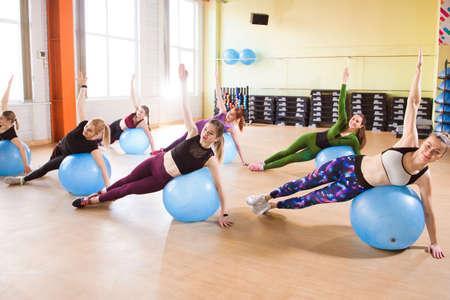 Foto de A group of young women go in for sports on fitness balls. - Imagen libre de derechos