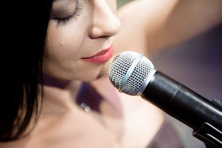 Photo pour Female singer, performing her vocal sound on the scene with spotlight. - image libre de droit