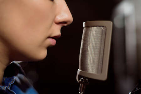 Photo for Close up of a singer recording a track in a studio - Royalty Free Image