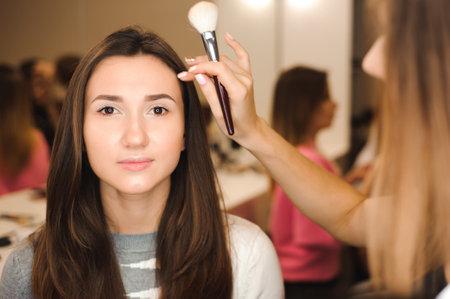 Photo pour Make up artist doing professional make up of young woman. Beauty shcool. - image libre de droit