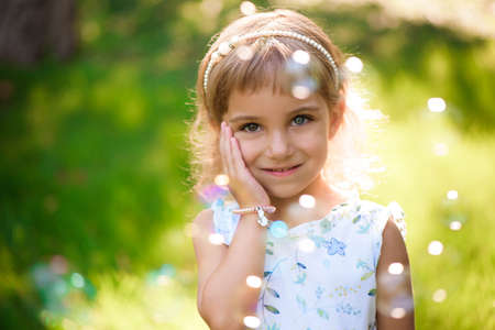 Photo for Sweet, happy, smiling five year old girl laying on a grass - Royalty Free Image
